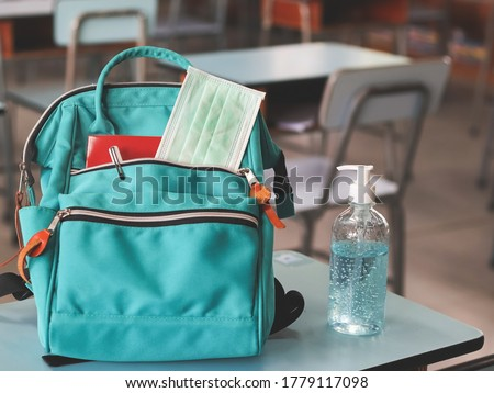 COVID-19 prevention , back  to school  and new normal  concept.Front view of  backpack with school supplies ,surgical mask and sanitizer gel on school desk in classroom. #1779117098
