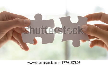 Close up view two female hands holding pieces join puzzles having fun play game. Connecting jigsaw, finding best match right solution, help in business, bond and mental connection, brain work concept Royalty-Free Stock Photo #1779157805