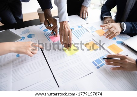 Close up table full of papers, diverse businesspeople analyzing report in charts and graphs discuss paperwork data statistics at group meeting. Research overview activity, brainstorm teamwork concept Royalty-Free Stock Photo #1779157874
