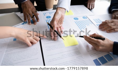 Diverse corporate staff discuss report shown in charts and graphs, analyzing financial stats, involved in project overview, reviewing results, close up. Employees participate in brainstorming concept Royalty-Free Stock Photo #1779157898