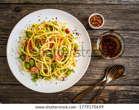 Spaghetti with broad bean, bacon and parmesan on wooden table  Royalty-Free Stock Photo #1779170699