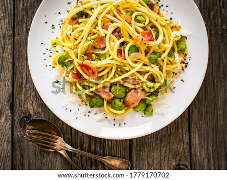 Spaghetti with broad bean, bacon and parmesan on wooden table  Royalty-Free Stock Photo #1779170702
