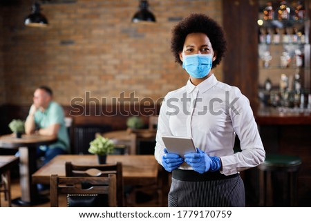 Portrait of black waitress wearing protective face mask while holding touchpad and looking at the camera in a pub.  #1779170759