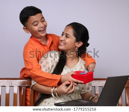 Cute Indian boy and girl celebrating raksha bandhan/ bhaidooj/ rakhi and exchanging gifts. Showing their bond of love. Spending family time on Indian festival. Fornt facing photo of brother sister duo