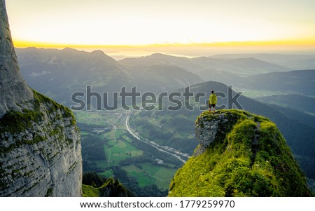 Hiker stands and enjoys valley view from hilly viewpoint. Traveling on hill peaks landscape. Sport, tourism and hiking concept. Watching sunset. #1779259970