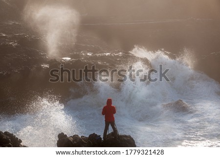 Fearless young female photographer taking pictures while surrounded by raging waves at rocky Oregon coast