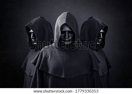 Group of three scary figures in hooded cloaks in the dark Royalty-Free Stock Photo #1779330353