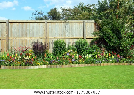Pretty Summer Flowers And Shrubs In A Well Maintained Garden. Royalty-Free Stock Photo #1779387059