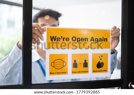 Asian businessman wear face mask attach reopen sign at office after lockdown due to coronavirus covid-19, business new normal and social distancing concept