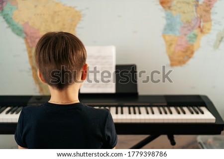 Young boy sitiing at digital piano. Playing keyboard, focused kid have activity at home. Hobby Royalty-Free Stock Photo #1779398786