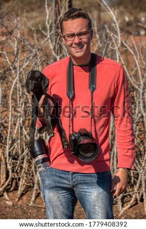 photographer taking pictures of a baby goat kid, in an african village, Botswana