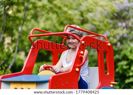 A seven-year-old boy sits on a wooden children's car in the summer. blurred background
