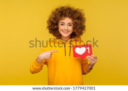 Internet blogging. Portrait of joyful curly-haired woman in urban style hoodie pointing at heart like icon, recommending to click on social media button. studio shot isolated on yellow background #1779427001