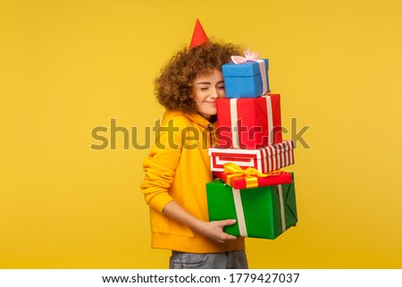 Happy emotions from big mountain of gifts. Portrait of pleased happy curly-haired woman with party cone embracing many present boxes, celebrating birthday. studio shot isolated on yellow background Royalty-Free Stock Photo #1779427037