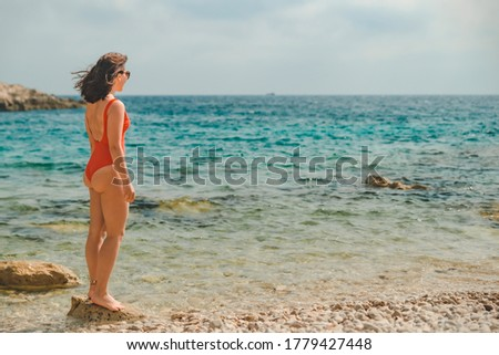 young pretty woman in red swimsuit looking at sea
