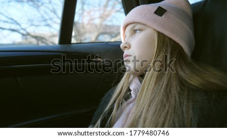 Beautiful female kid with long blonde hair looks outside through the window in the backseat of a moving car. Small sad girl rides on modern SUV and watches at nature through the glass of auto. Slow mo