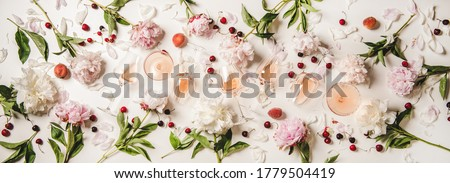 Rose wine variety layout. Flat-lay of rose wine in various glasses with flowers and summer fruit over plain white background, top view. Summer drink for party, wine shop or wine tasting concept #1779504419