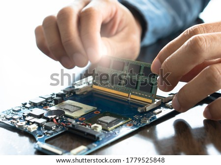 Abstract of electronic engineer of computer technology. Maintenance computer cpu hardware upgrade of motherboardputting the CPU on the socket of the computer motherboard. #1779525848