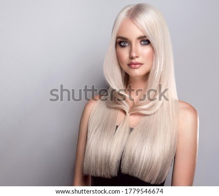 Beautiful girl with dyed  long hair in blond. Stylish hairstyle  done in a beauty salon. Beauty, cosmetics and makeup
