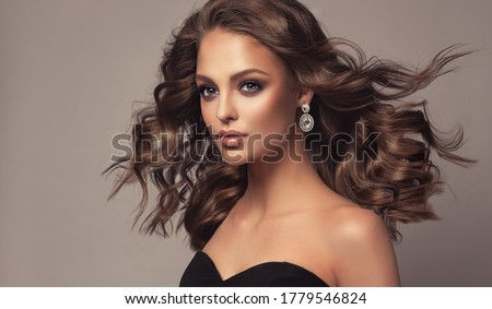 Beautiful model girl with wavy and shiny hair . Brunette woman with curly hairstyle,earrings and jewelry Royalty-Free Stock Photo #1779546824