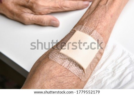 Wound bandage, Dressing arm wound with sterile plaster pad, Accidental wound care treatment in elder old man. #1779552179