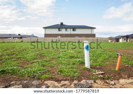 Vacant land next to some residential suburban houses. Concept of real estate development, land for sale and a new suburb, Tarneit, Melbourne, VIC Australia. Royalty-Free Stock Photo #1779587819