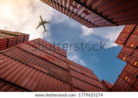 Airplane flying above container logistic. Cargo and shipping business. Container ship for import and export logistic. Logistic industry from port to port. Container at harbor for truck transport.  #1779625274