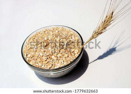 Bowl full of oats. Porridge oats in  cereal bowl on white background. A bowl of whole oats isolated on a white background. Healthy Eating concept-Oat Flakes. #1779632663
