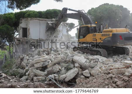 Urban Regeneration. Demolition of a building for new construction. Dismantling of a house. Excavator demolishing barracks for new construction project. Urban Renewal‎. Royalty-Free Stock Photo #1779646769