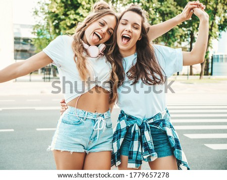 Portrait of two young beautiful smiling hipster women in trendy summer white t-shirt clothes.Sexy carefree women posing on street background. Positive models having fun, hugging and going crazy #1779657278