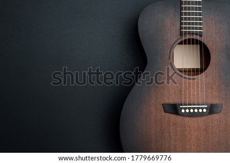 Acoustic guitar on black background. Space for text.