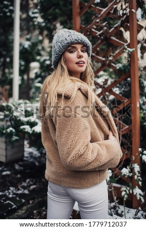 Back view of stylish female in warm outerwear standing in snow covered park and looking over shoulder at camera in winter day Royalty-Free Stock Photo #1779712037