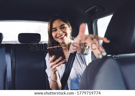 Cheerful smiling young female passenger in casual outfit sitting in car backseat with seatbelt fastened and using smartphone while giving direction to driver and pointing with finger #1779719774