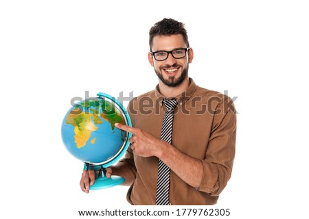 Bearded teacher smiling at camera while pointing with finger at globe isolated on white