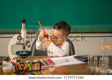 one asia boy is watching his sharp of orange pencil in red pencil sharpener with Scientific equipment. back to school concept on photography image.