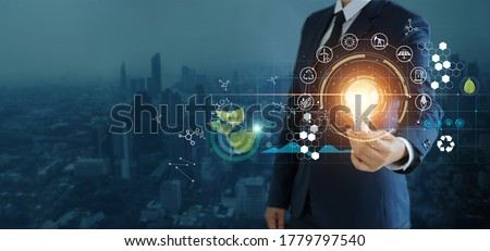 businessman holding light bulb against nature on city background  with icons energy sources for renewable, sustainable development,  Ecology and renewable energy concept. Royalty-Free Stock Photo #1779797540