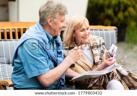 Happy senior couple with photo album looking through family pictures on camping trip
