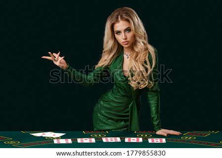 Girl in stylish dress is showing something, leaning on playing table with cards on it, posing on green background. Poker, casino. Close-up, copy space Royalty-Free Stock Photo #1779855830