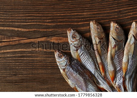 Dried or jerky salted roach, clipfish on wooden background. Salty beer appetizer. Traditional way of preserving fish. Close up