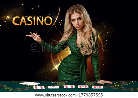Lady in green dress is showing inscription casino, leaning on playing table with cards on it, posing on black background. Poker, casino. Copy space #1779857555