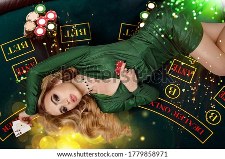 Blonde female in green dress is showing red chips and aces. Lying on playing table with colorful sparkles above her. Poker, casino. Close-up, top view Royalty-Free Stock Photo #1779858971