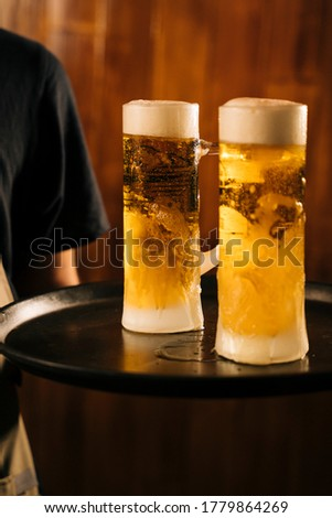 Waiter with two cold beer mugs on the tray