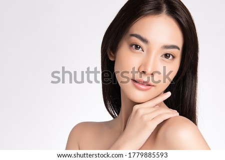 close up Beauty face. Smiling asian woman touching healthy skin portrait. Beautiful happy girl model with fresh glowing hydrated facial skin and natural makeup on white background, Royalty-Free Stock Photo #1779885593