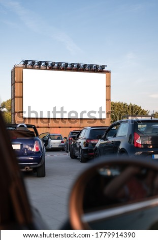 Perspective of a cinema drive in parking with cars parked in front of a big white screen to watch movies or films inside the car. Open air public Cinema drive-in. Social Distance, covid-19 #1779914390