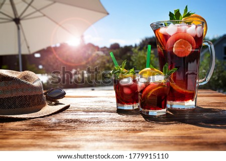 Jug fresh cold summer drink on a sunny terrace with parasol and straw hat on wooden table. Background for vacation and leisure. Short depth of field. Royalty-Free Stock Photo #1779915110