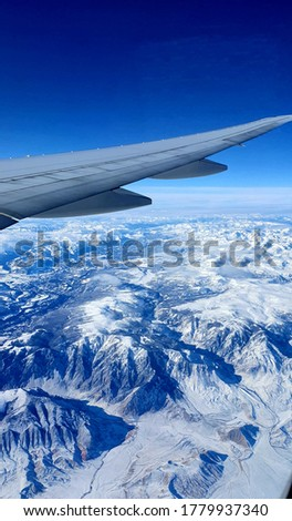View from a plane, snow Mountains photographed from a plane window holiday pictures plane pictures snow top Mountains blue sky