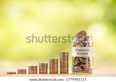 "A glass jar with text label ""financial freedom"" filled with coins placed beside a pile of coins. Saving money for financial independence or financial freedom concept. Royalty-Free Stock Photo #1779981155"