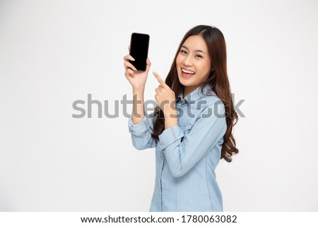 Portrait of Asian woman showing or presenting mobile phone application and pointing finger to smartphone on hand isolated over white background, Asian Thai model #1780063082