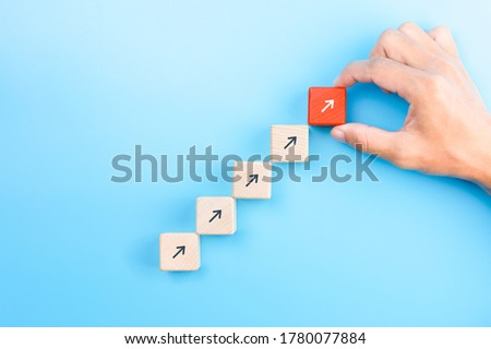 Businessman hand arranging wooden blocks stacking as step stair with arrow up, Business growth success process concept, copy space Royalty-Free Stock Photo #1780077884