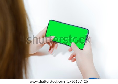 contactless in new normal concept from woman hold and use smart phone with green screen and white isolated background